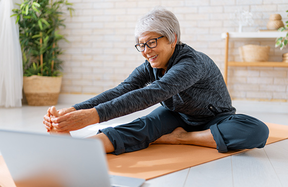 Woman on yoga mat with computer